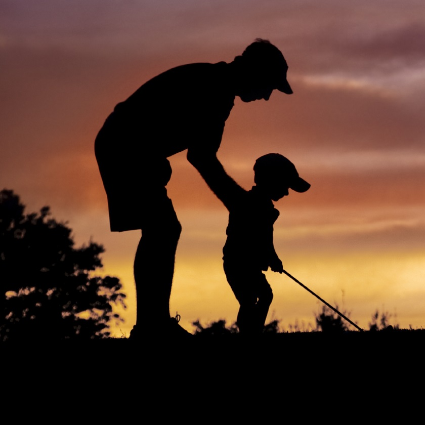father and son golfing at sunset